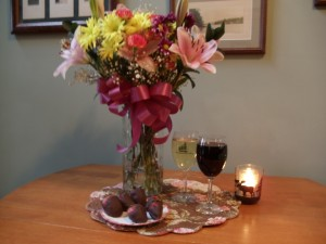 flowers in a vase, wines, and chocolate-covered strawberries